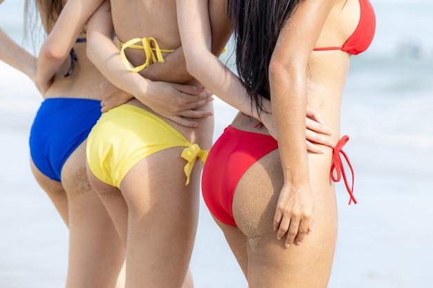 Aziatische vrouwenvrienden bij het strandmening van rug, groep van drie mooie hete jonge vrouwen op het strand in sexy bikini.