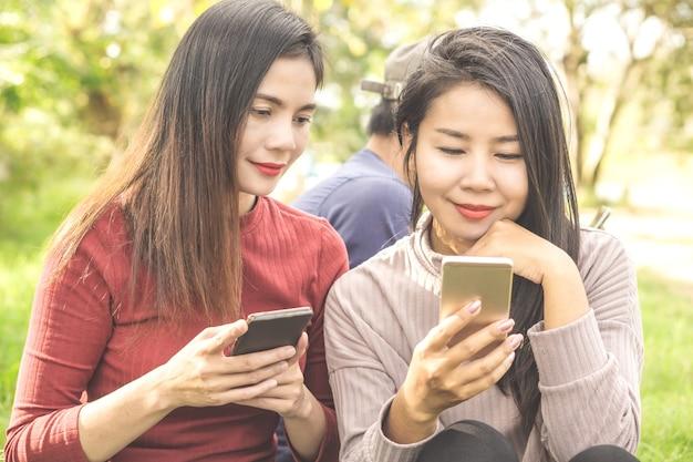 Aziatische vrouwenvrienden die in een park zitten die slimme telefoon met behulp van
