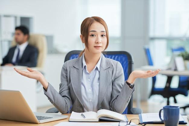 Aziatische vrouwenzitting bij bureau in bureau en het bekijken camera met hulpeloos handgebaar