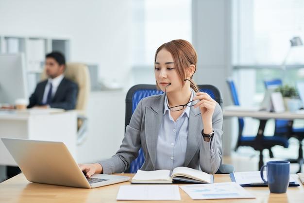 Aziatische vrouwenzitting bij bureau in bureau, holdingsglazen en het werken aan laptop