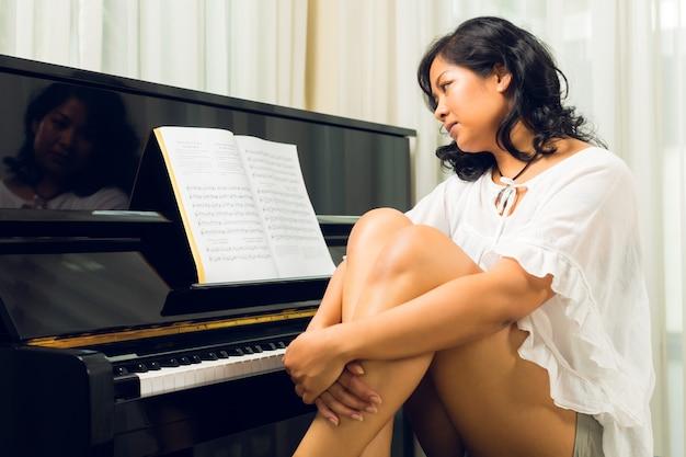 Aziatische vrouwenzitting bij de piano