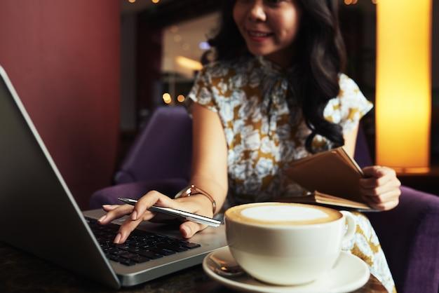 Aziatische vrouwenzitting in koffie en het werken met laptop, en kop van cappuccino op lijst