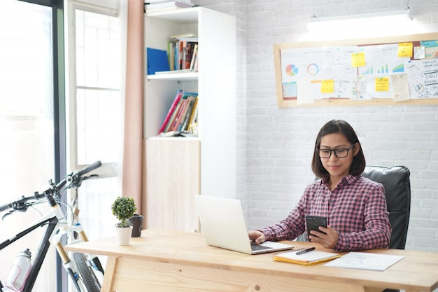Aziatische vrouwenzitting in modieuze holdingssmartphone met het werken aan laptop in huisbureau