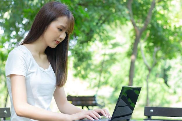 Aziatische vrouwenzitting met laptop in een park