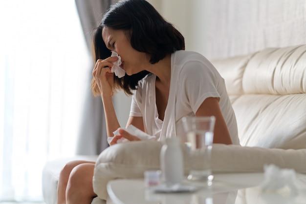 Aziatische vrouwenzitting op bank die thuis koude koorts hebben die weefsel gebruiken om haar neus schoon te maken.