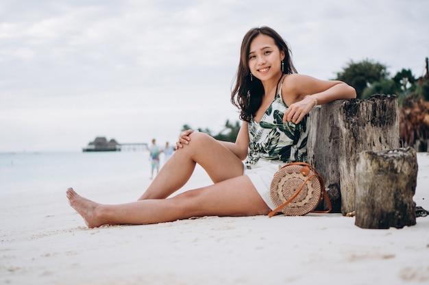 Aziatische vrouwenzitting op wit zand door de indische oceaan