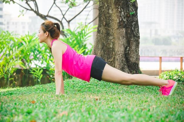 Aziatische vrouwopwarming om door lichaamsgewichtdrukknop op groene gazons in park uit te oefenen