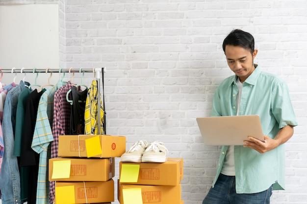 Aziatische werkende laptop van de mensentribune computer op bakstenen muur