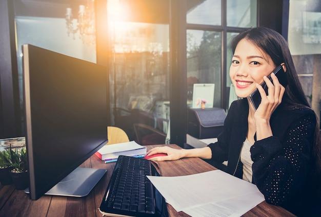 Aziatische werkende vrouw gebruikend computer in huisbureau en sprekend op mobiele telefoon met gelukgezicht
