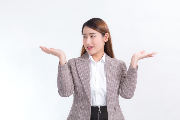 Aziatische werkende vrouw lacht en toont haar handen om iets op de witte achtergrond te presenteren.