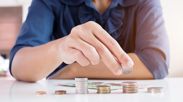 Aziatische werkende vrouwen die muntstukken tellen en geld besparen voor financiële planning.
