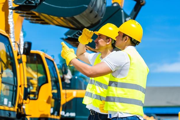Aziatische werknemer bij bouwmachines van bouwplaats