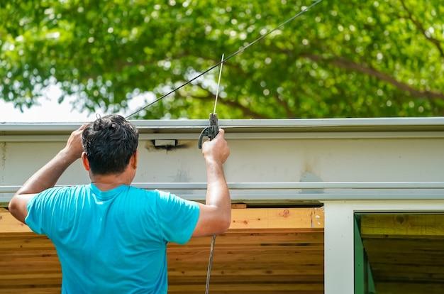 Aziatische werknemer last de stalen stok om een constructie te creëren voor de waterafvoer op het dak
