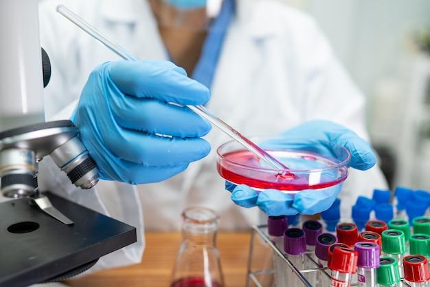 Aziatische wetenschapper die onderzoek doet met een microscoop in laboratorium.