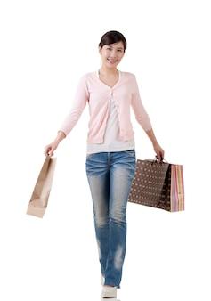 Aziatische winkelen vrouw met zakken, volledige lengte portret met reflectie in studio witte achtergrond.