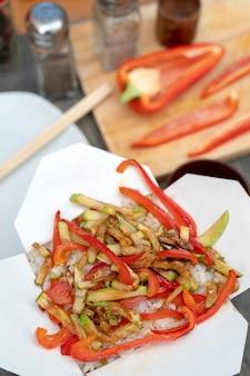 Aziatische witte rijst met groenten in een kartonnen doos.