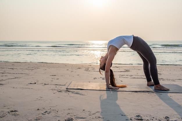 Aziatische yogavrouw die oefening op het strand doet.