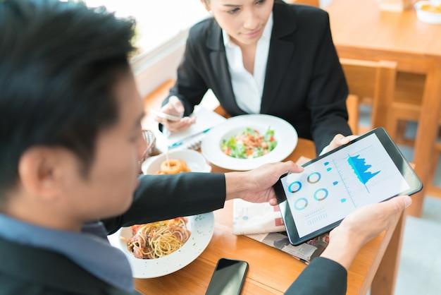 Aziatische zakelijke pauze voor de lunch in een restaurant