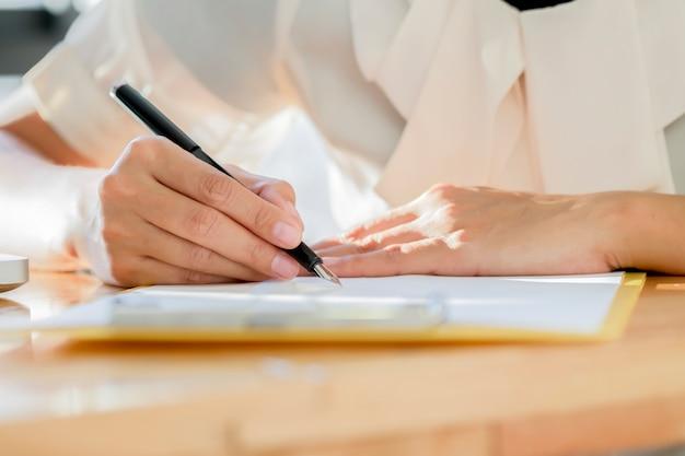 Aziatische zakelijke vrouw ondertekend een contract document een overeenkomst maken.