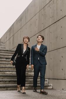 Aziatische zakelijke vrouwen en mannen lopen en praten samen