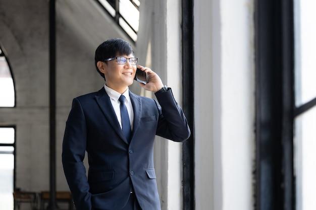 Aziatische zaken in brillen staan op het raam en gebruiken een smartphone om zaken te doen, een zakenman in een formeel pak die lacht met behulp van een slimme telefoon.