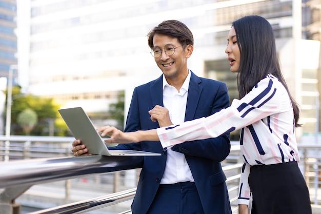 Aziatische zaken man en vrouw die werken op laptopcomputer staan buiten kantoorgebouw.
