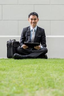 Aziatische zaken man met behulp van draagbare computer op het park van de stad. hij kijkt