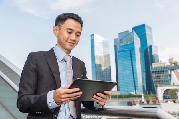 Aziatische zaken man met behulp van draagbare computer op stad. hij glimlacht