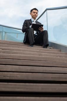 Aziatische zaken man met behulp van draagbare computer op trappen. hij is aan het werk