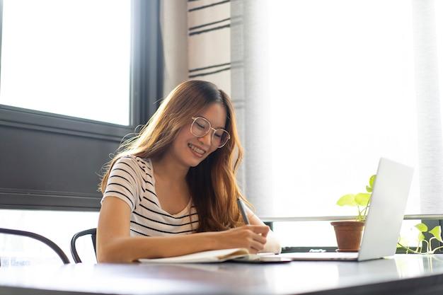 Aziatische zaken meisje opstarten werken met laptop in café