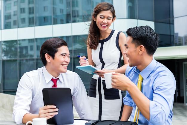 Aziatische zaken vrouw en mannen buiten werken op computer koffie drinken