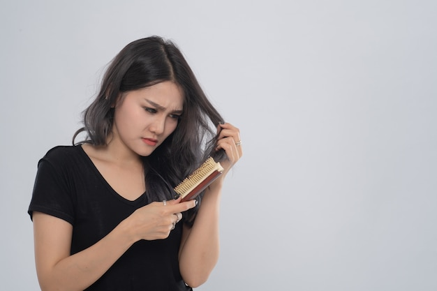 Aziatische zaken vrouw met een kam en probleem haar op grijze achtergrond