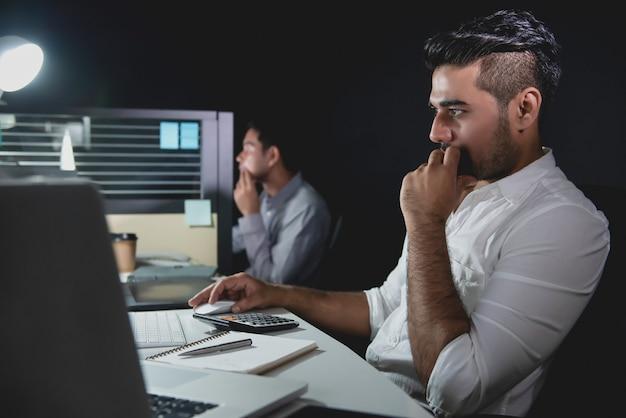 Aziatische zakenlieden die overuren laat bij nacht blijven die in het bureau werken