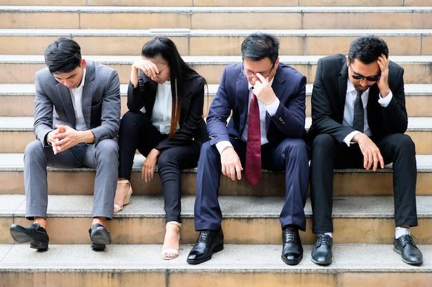 Aziatische zakenlieden die somber wegens werkloosheid zitten.
