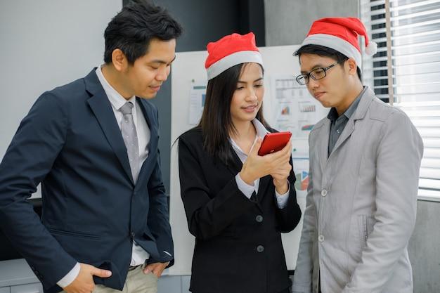 Aziatische zakenlieden en groep die mobiele telefoon voor partners met behulp van die documenten en ideeën bespreken op vergadering en bedrijfsvrouwen glimlachen gelukkig voor het werken