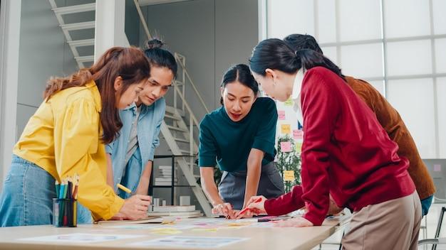 Aziatische zakenlieden en vrouwelijke ondernemers brainstormen over creatieve webdesign planningstoepassing en het ontwikkelen van sjabloonlay-out voor mobiele telefoonproject samen te werken in een klein kantoor.