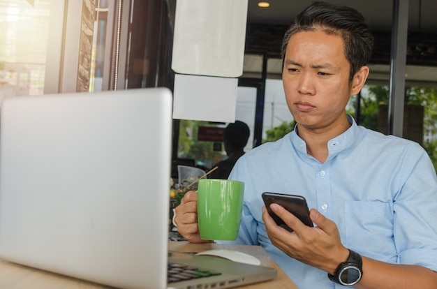 Aziatische zakenlieden houden een mobiele telefoon vast, kijken naar gegevens op de computer en maken zich zorgen over hun werk