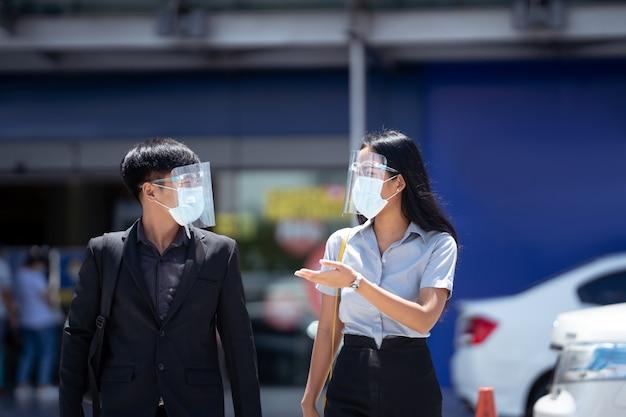 Aziatische zakenlieden praten met afstand, ze dragen een gelaatsscherm.