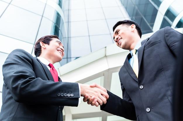 Aziatische zakenluihanddruk voor de hoge stijgingsbouw