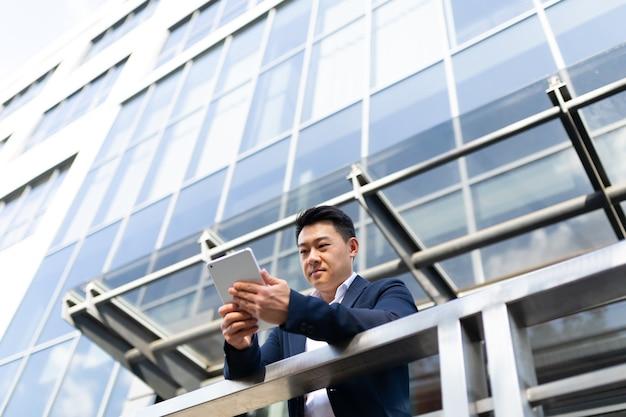 Aziatische zakenman baas leest het nieuws van een tabletcomputer, staande in de buurt van zijn kantoorcentrum op het balkon in een donkere kleur