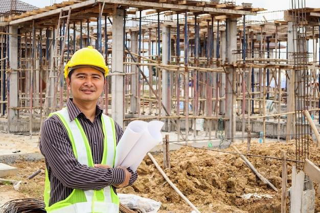 Aziatische zakenman bouw ingenieur werknemer in beschermende helm en blauwdrukken papier bij de hand op huis bouwplaats