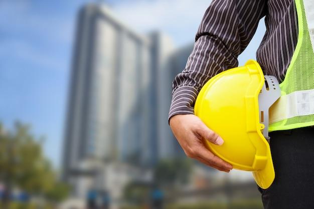 Aziatische zakenman bouwingenieur of architect werknemer met gele beschermende helm op groot condominium bouwterrein