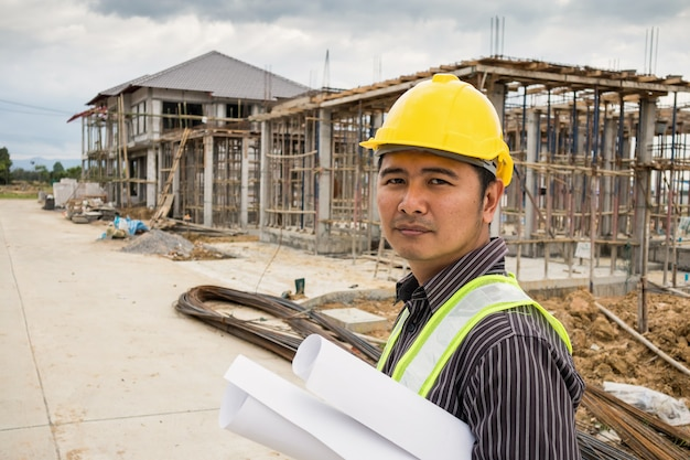 Aziatische zakenman bouwingenieur werknemer in beschermende helm en blauwdrukken papier bij de hand op huis bouwplaats