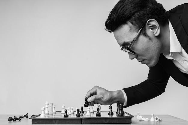 Aziatische zakenman denkt na over zijn volgende zet op het schaakbord
