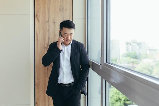 Aziatische zakenman die aan de telefoon in een modern kantoorcentrum praat, belt naar collega's