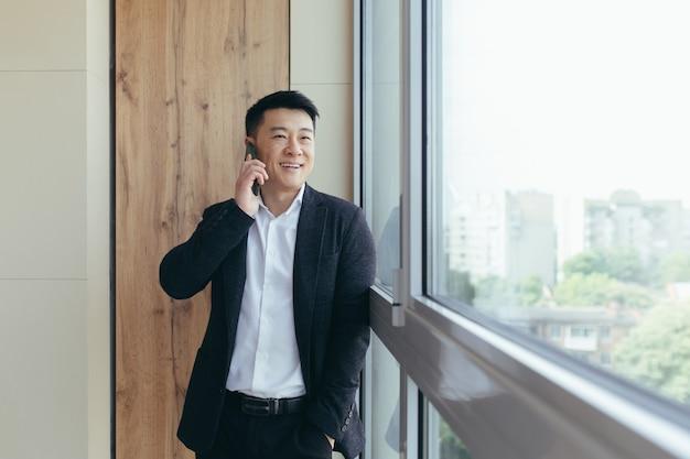 Aziatische zakenman die aan de telefoon praat in een modern kantoorcentrum en goed nieuws deelt met metgezellen