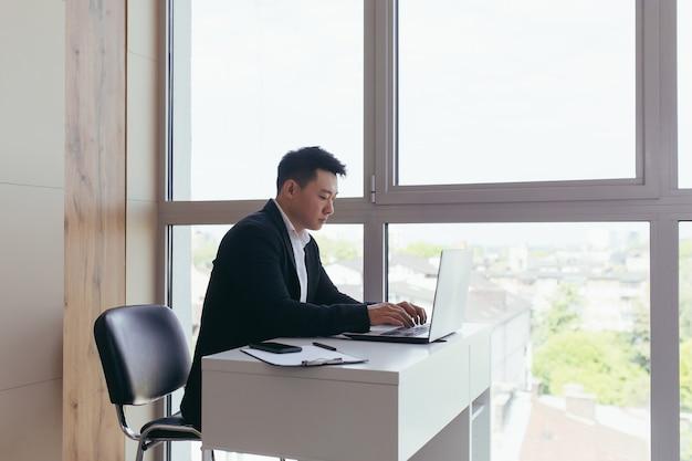 Aziatische zakenman die aan laptop werkt die in modern bureau zit