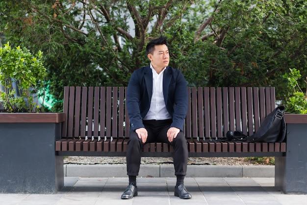 Aziatische zakenman die ademhalingsoefeningen uitvoert om stress te kalmeren, zittend op een bank tijdens een lunchpauze in een pak
