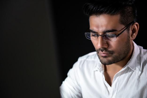 Aziatische zakenman die bij het werken bij nacht concentreert zich