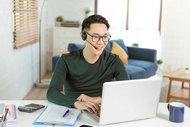 Aziatische zakenman die computerlaptop en hoofdtelefoon met behulp van die voor videogesprekconferentievergadering spreken. werk vanuit huis concept.